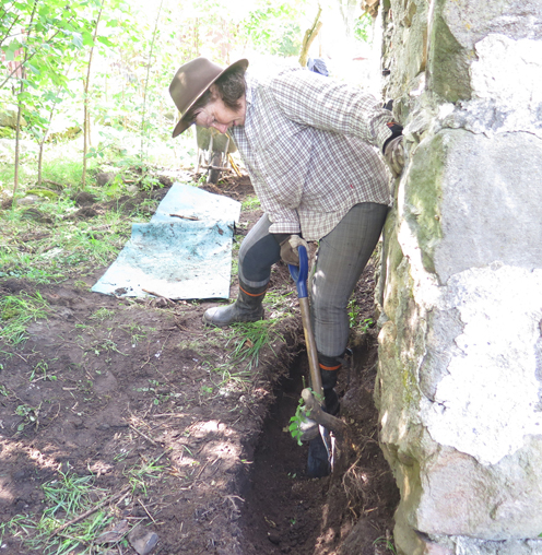 Lotta gräver  bort rötter under huset