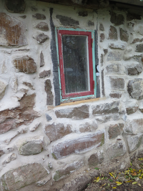 Resturerat fönster om stenvägg